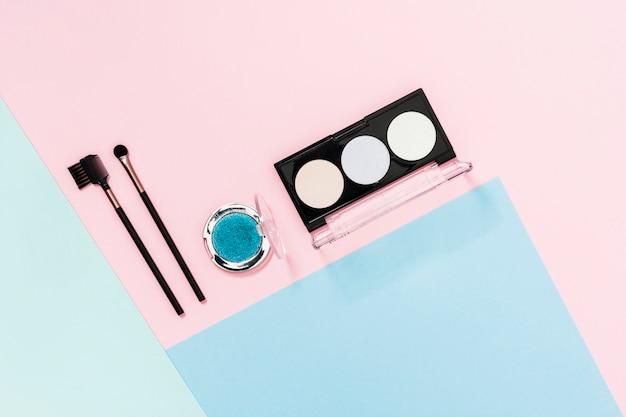 色付きの背景上の化粧ブラシとアイシャドウパレット 無料写真