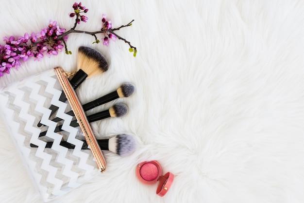化粧ブラシと白い毛皮のピンクのコンパクトフェイスパウダーと紫の小枝 無料写真