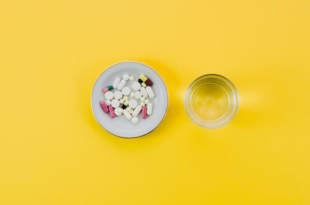 Медицинские таблетки в миску и стакан воды на желтом фоне Бесплатные Фотографии