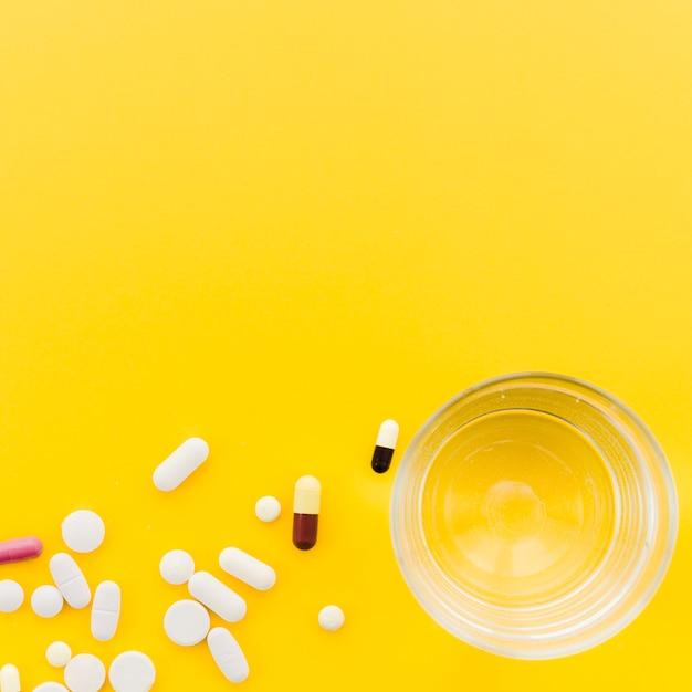 Многие таблетки и капсулы возле стакана воды на желтом фоне Бесплатные Фотографии
