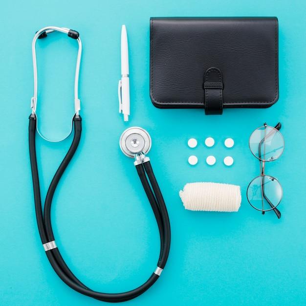 Стетоскоп; ручка; таблетки; дневник; очки и повязка на синем фоне Бесплатные Фотографии