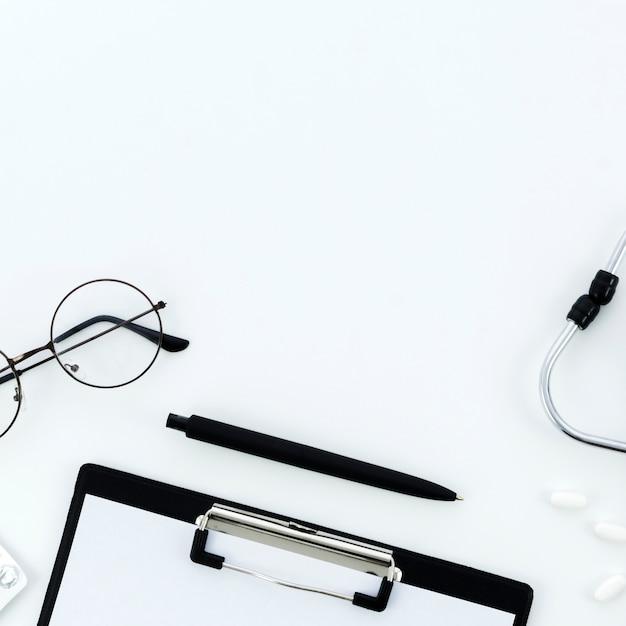 Очки; ручка; буфер обмена; таблетки и стетоскоп на белом фоне Бесплатные Фотографии