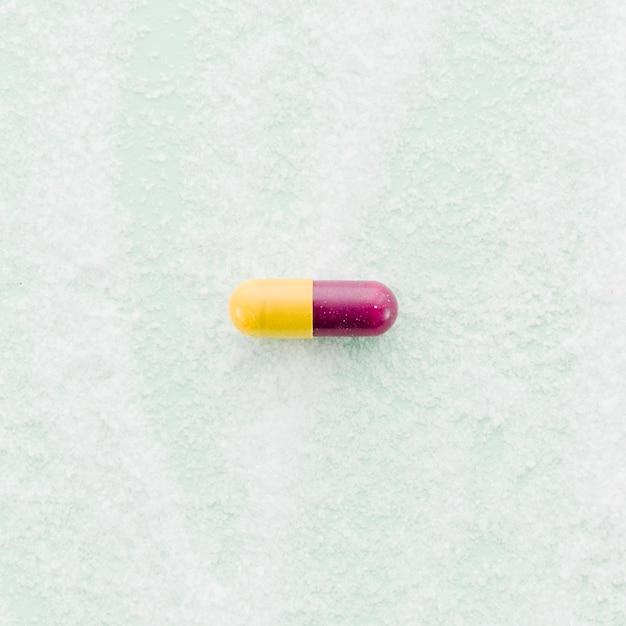 Красные и желтые капсулы на текстурированном фоне Бесплатные Фотографии