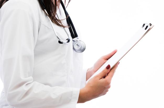白い背景に対して手で女医の保持クリップボードの側面図 無料写真