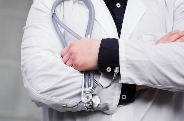 聴診器を手で保持している男性の医者の手の中間セクション 無料写真
