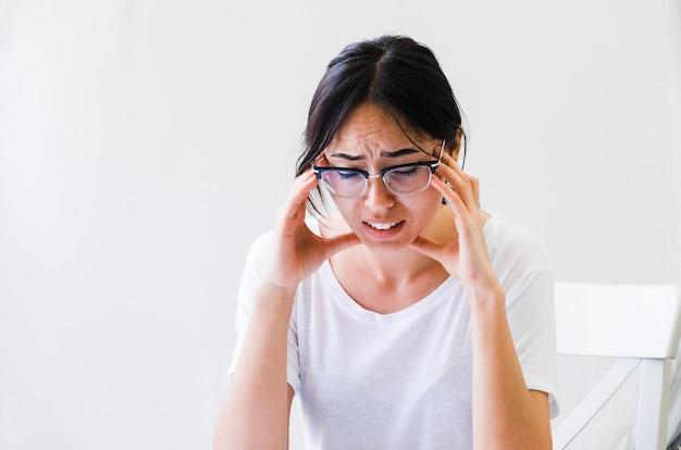 白い背景で隔離の頭痛に重度の痛みを持つ女性のクローズアップ 無料写真