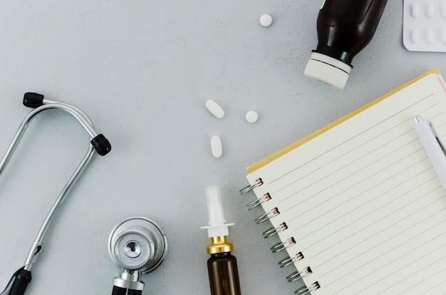 聴診器ピル;ボトル;鼻スプレー日記と灰色の背景上のペン 無料写真