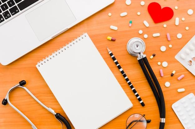 赤いハートを持つ多くのカラフルな丸薬。聴診器鉛筆;眼鏡と木製の机の上のノートパソコン 無料写真