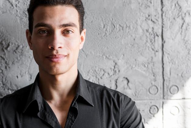 壁に立っている笑顔の若い男の肖像 無料写真