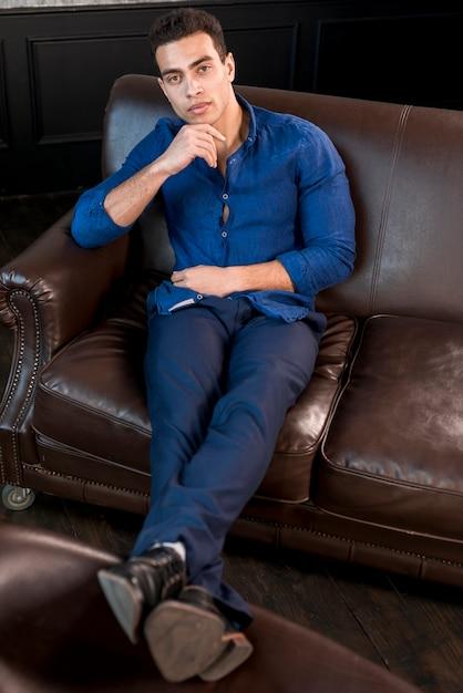 Поднятый вид красивый молодой человек, сидя на коричневой диван с рукой на его подбородок, глядя на камеру Бесплатные Фотографии