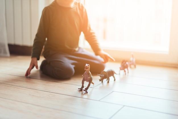 Малыш играет с игрушечными динозаврами Бесплатные Фотографии