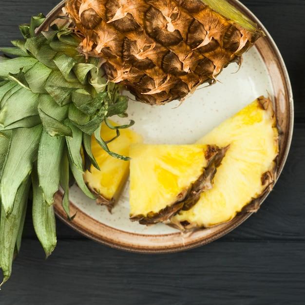 Ломтики ананаса с зелеными листьями на тарелке Бесплатные Фотографии