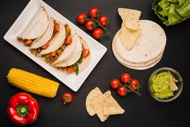 野菜とソースの近くの皿の上のタコス 無料写真