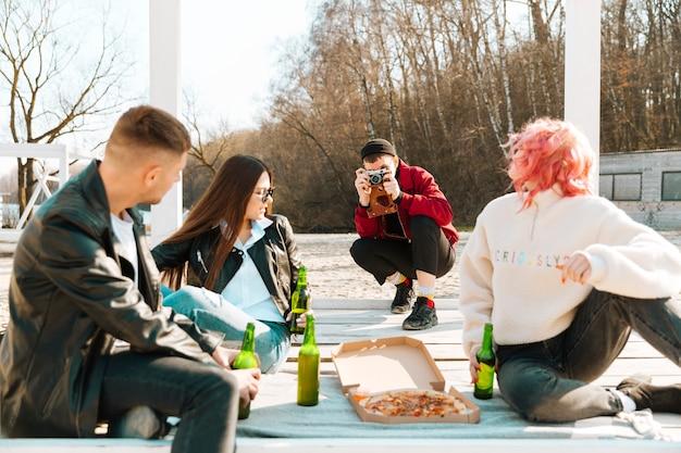 Счастливые друзья фотографировать и устраивать вечеринки на открытом воздухе Бесплатные Фотографии