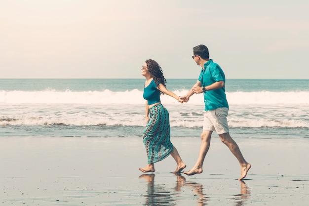 ビーチに沿って歩く裸足カップルの笑顔 無料写真
