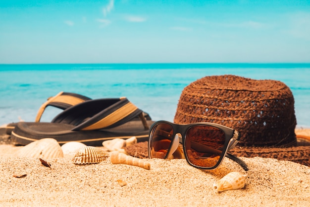 砂浜で帽子とフリップフロップのサングラス 無料写真