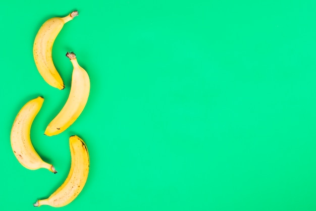 Желтые бананы на зеленом фоне Бесплатные Фотографии
