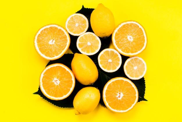 黄色の背景に葉の上の柑橘系の果物のセット 無料写真