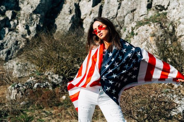 Крутая молодая женщина, завернутая в флаг, стоящий в природе Бесплатные Фотографии