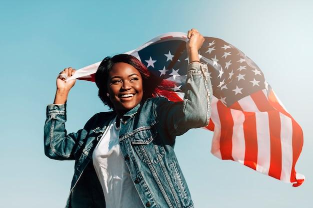 アメリカの国旗と手を上げる黒の笑顔の女性 無料写真