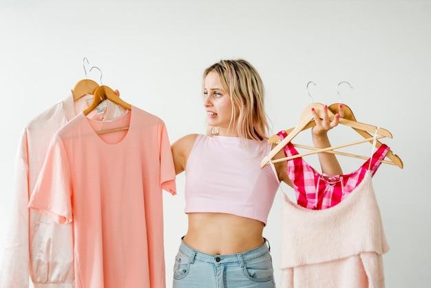 Светловолосый влияющий держит розовую одежду Бесплатные Фотографии