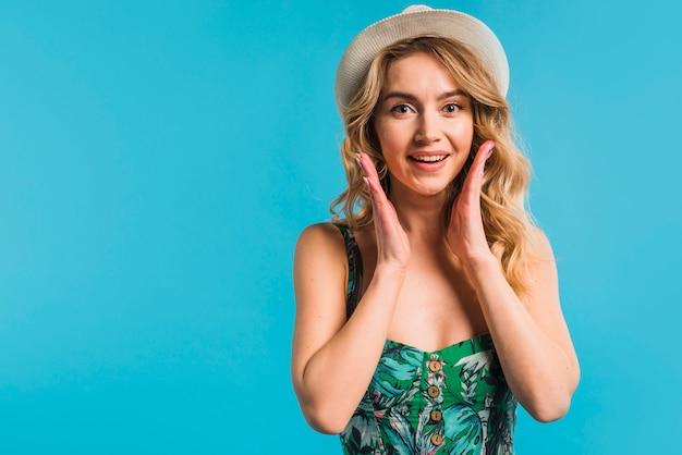 花の咲くドレスと帽子でびっくりした魅力的な若い女性 無料写真