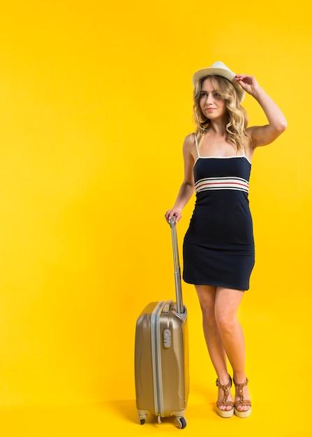 Счастливая молодая женщина с чемоданом, глядя Бесплатные Фотографии