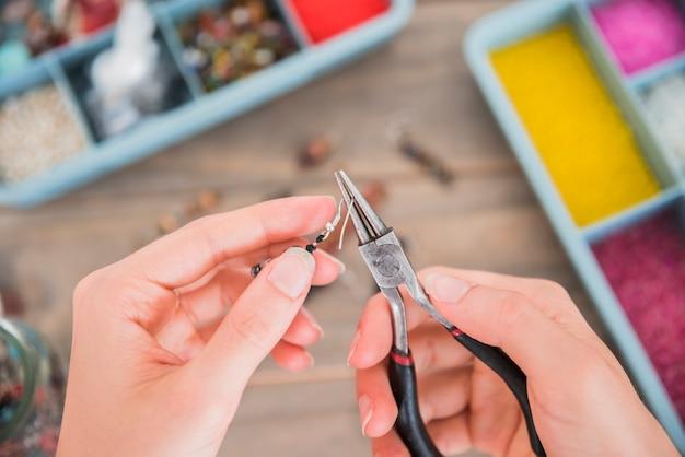 木製の机の上のペンチでイヤリングフックを修正する女性の俯瞰 無料写真