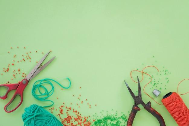 赤と緑のビーズ。はさみ;ペンチと緑色の背景でスプール 無料写真