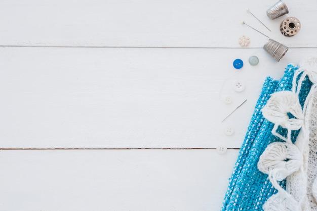 Ручная вязка крючком; кнопки; иглы и наперсток на белом деревянном столе Бесплатные Фотографии