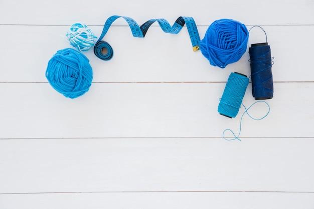 ブルーウールボール。木製の机の上の測定テープとスプール糸 無料写真