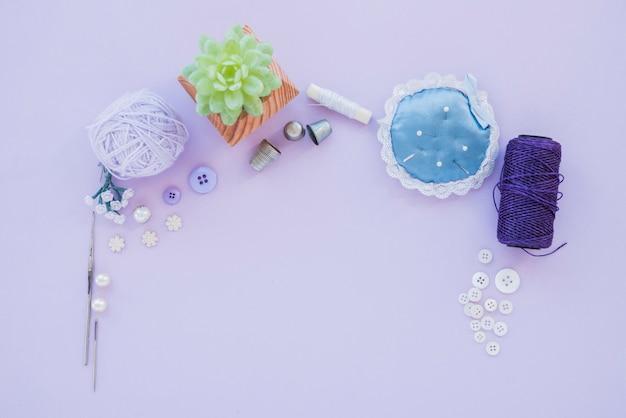 Иглы с подушечкой для булавок; наперсток; шерстяной шарик; бисер; пуговица и пряжа на фиолетовом фоне Бесплатные Фотографии
