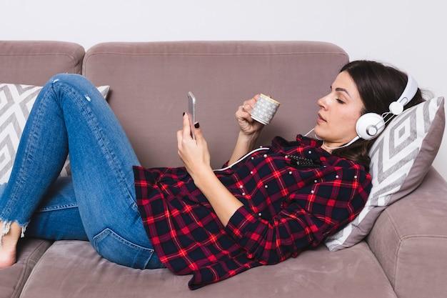 ヘッドフォンで音楽を聴くのソファに横になっている若い女性 無料写真