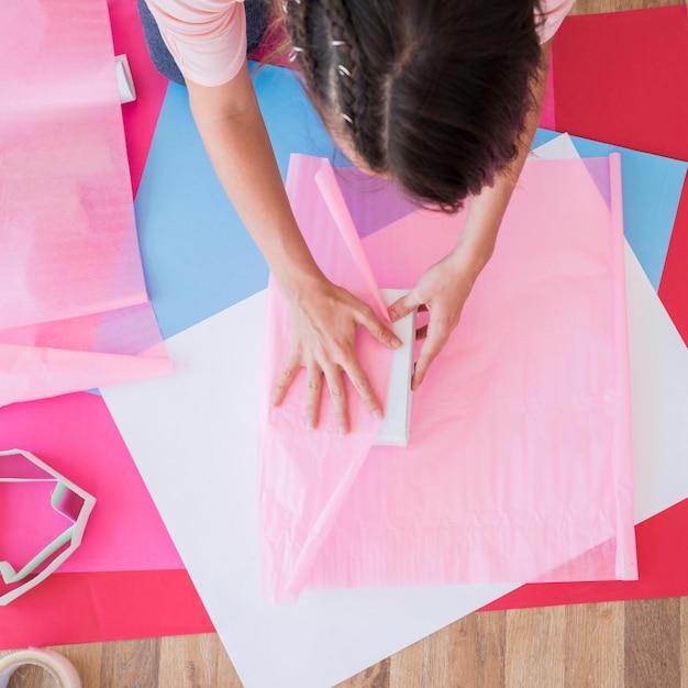 テーブルの上のカード紙にピンクの紙で箱を包む女性の高角度のビュー 無料写真