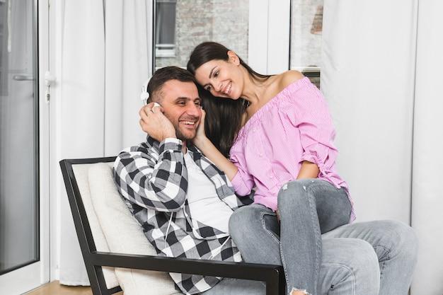 ヘッドフォンで音楽を聴く彼女のボーイフレンドの膝の上に座っている若い女性 無料写真