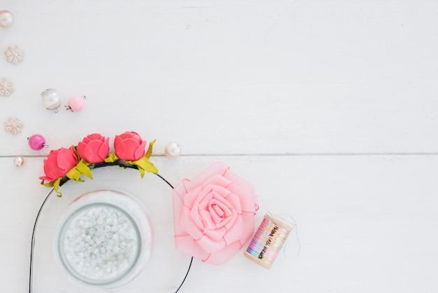 バラのヘアバンド。ビーズ;スライバースプールと木製の背景上のリボンで作られたピンクのバラ 無料写真