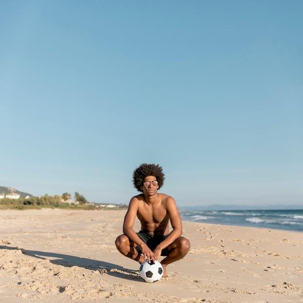 ビーチでボールとリラックスした黒人男性 無料写真
