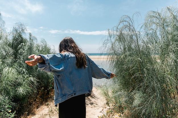 手を離れて茂みに立っている女性 無料写真