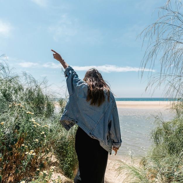 熱帯の茂みで上げられた手の地位を持つ女性 無料写真