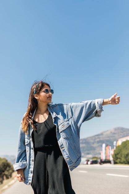 日当たりの良い道路でヒッチハイクの若い女性 無料写真