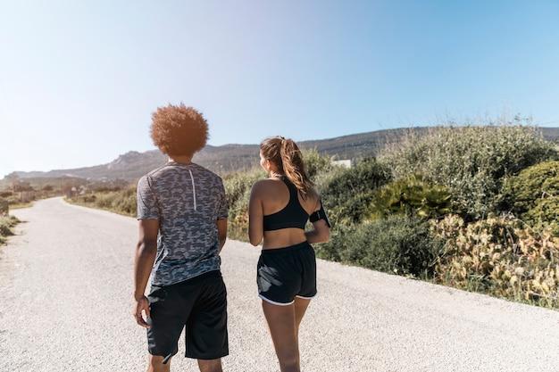 男と女の道に沿って歩くスポーツウェア 無料写真