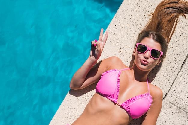 Молодая женщина кладя бассейном и показывая жест мира Бесплатные Фотографии