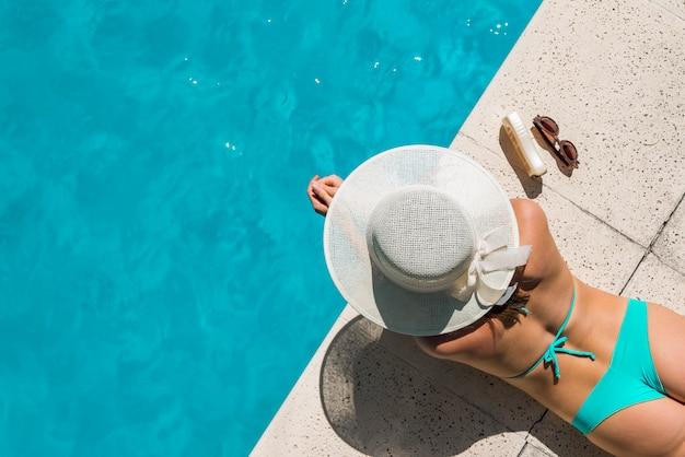 プールサイドで日光浴ビキニの若い女性 無料写真