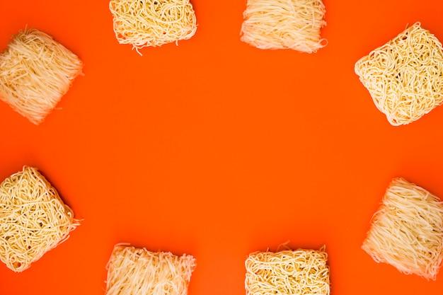 オレンジ色の背景上のさまざまな生麺ブロックで作られたフレーム 無料写真