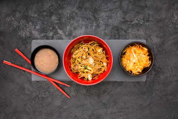 新鮮な麺ソースとサラダ黒の石の背景の上にボウルで提供しています 無料写真