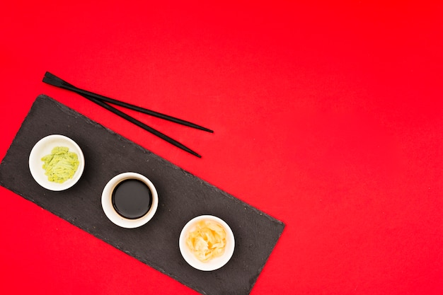 赤いテーブルの上の黒い石の上にボウルとお箸で生姜のマリネとさまざまなおいしいソース 無料写真
