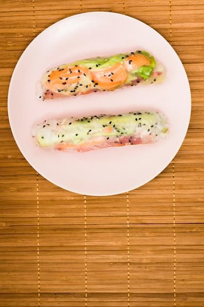 Повышенный вид азиатских блинчиков с начинкой с лососевых рыб и овощей на белой тарелке над столовой Бесплатные Фотографии