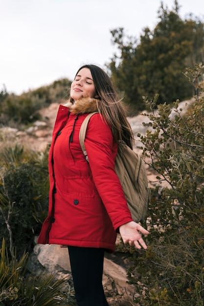 山で新鮮な空気を楽しんでいる彼女のバックパックを持つ若い女 無料写真