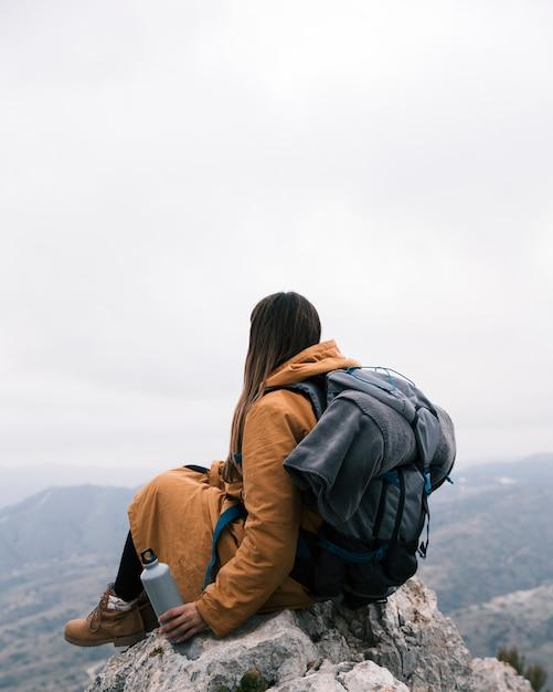 ビューを見て手でボトルを保持している山の頂上に座っている女性ハイカー 無料写真