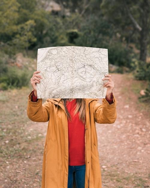 彼女の顔の前で地図を保持している若い女性 無料写真